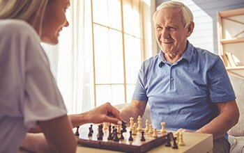 Elderly Care — Staff playing chess with an elder in Columbia, SC